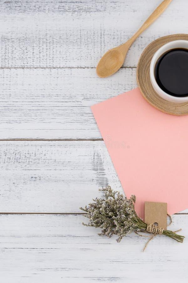 Tarjeta rosada en blanco y una taza de café con el ramo del caspia fotografía de archivo libre de regalías