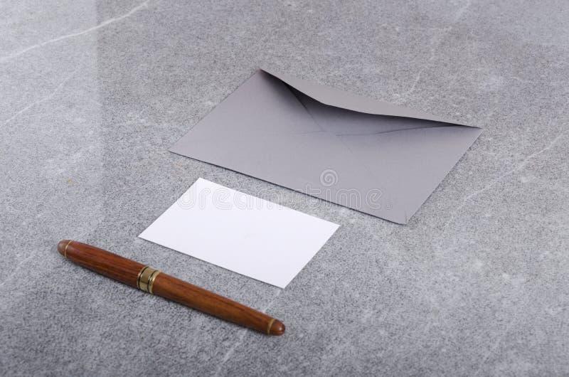 Tarjeta, sobre y pluma en blanco de los bisines en la superficie gris Concepto de fuentes de lujo del negocio foto de archivo
