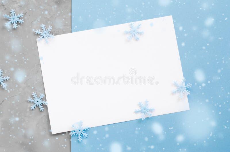 Tarjeta vacía de la Navidad con los copos de nieve decorativos en color azul imagen de archivo libre de regalías