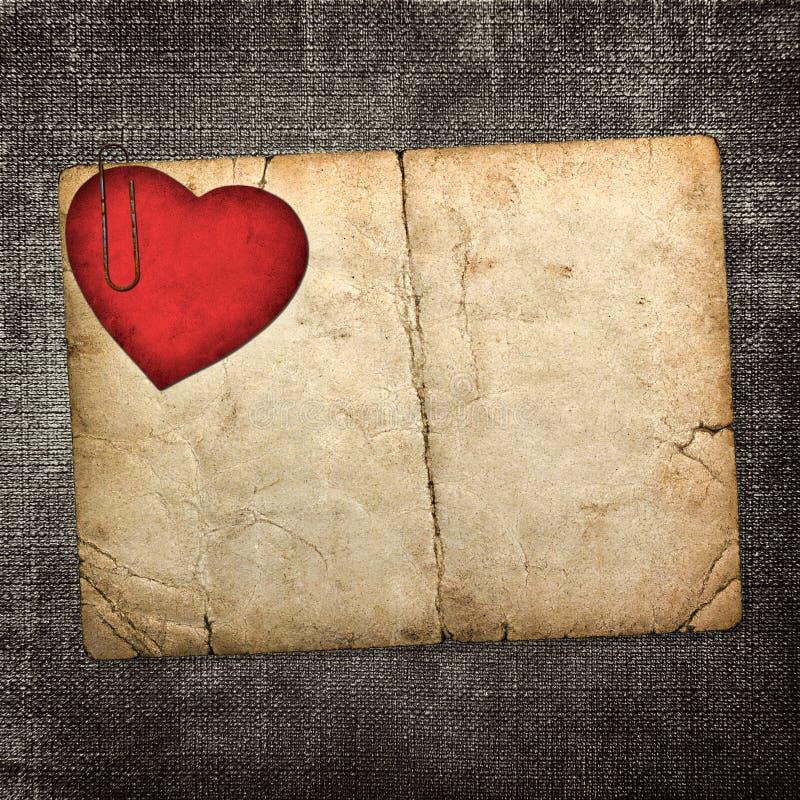 Tarjeta vieja del cartón con el corazón de papel rojo en un backgr oscuro de la tela imágenes de archivo libres de regalías