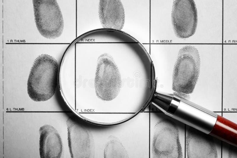 Tarjeta y lupa criminales de la huella dactilar fotos de archivo