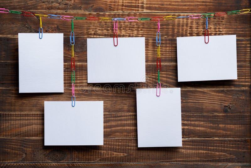 Tarjetas blancas en blanco que cuelgan en cadena de clip en un fondo de madera, una plantilla para un collage de la foto, un conc foto de archivo libre de regalías