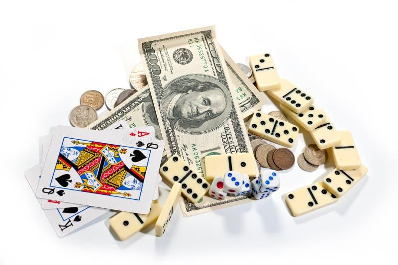 Tarjetas, dados, dominós y dinero en un fondo blanco imagen de archivo