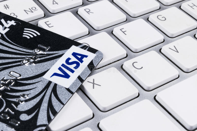 Tarjetas de crédito de la VISA en el teclado de ordenador en oficina imagenes de archivo
