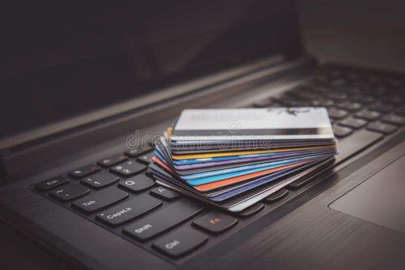 Tarjetas de crédito en el teclado de ordenador imagenes de archivo