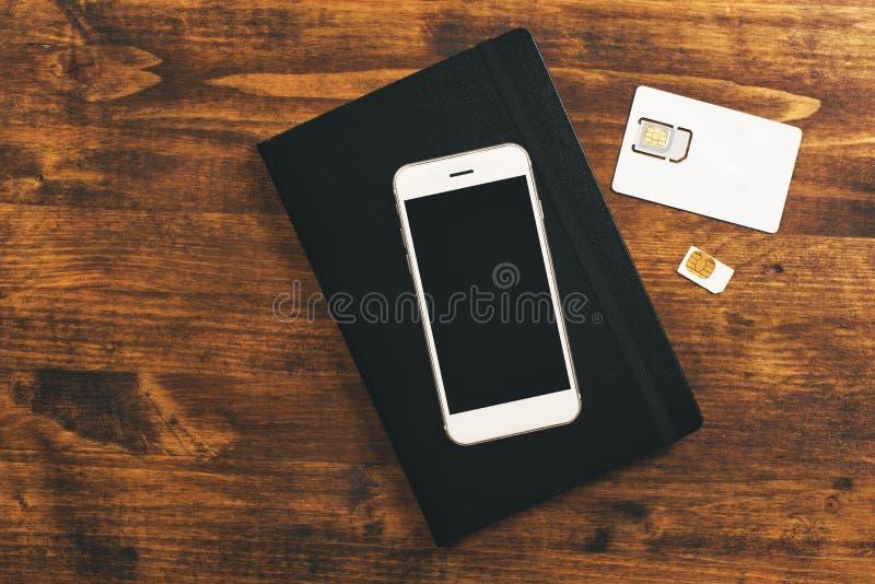 Tarjetas de la transferencia SIM en smartphone móvil imagenes de archivo