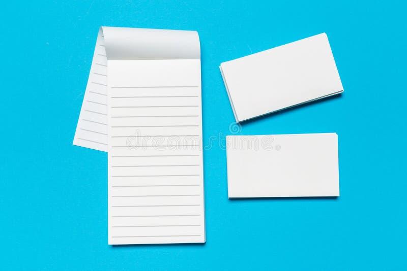 Tarjetas de visita blancas en blanco en fondo azul Maqueta para la identidad de marcado en caliente imagenes de archivo