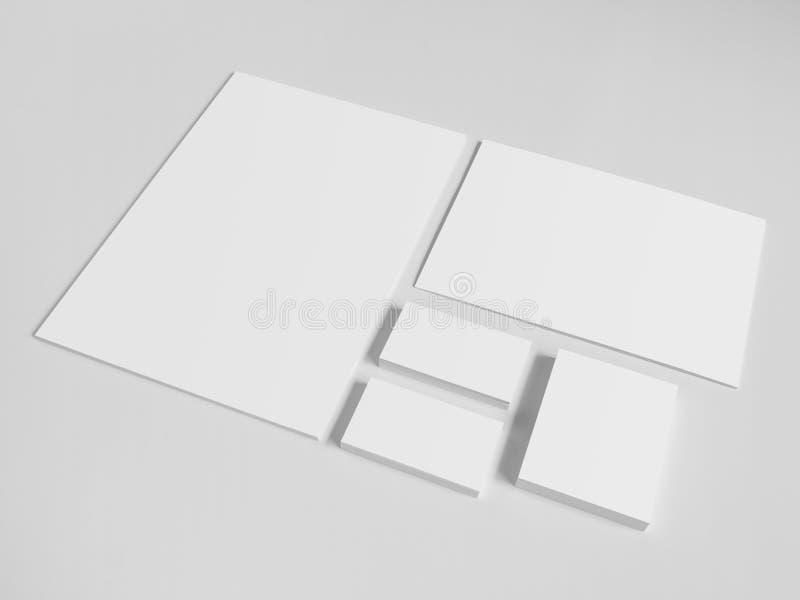 Tarjetas de visita en blanco con una pila de papeles y foto de archivo