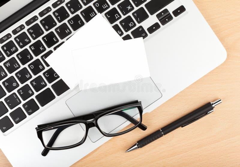 Tarjetas de visita en blanco sobre el ordenador portátil en la tabla de la oficina imagen de archivo libre de regalías