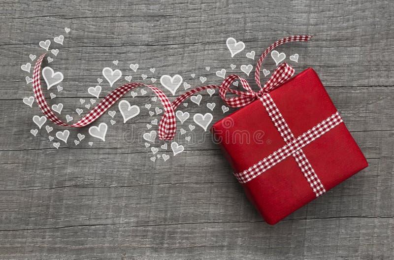 Tarjetas del día de San Valentín rojas presentes con la cinta y los corazones comprobados en el wo gris fotos de archivo libres de regalías