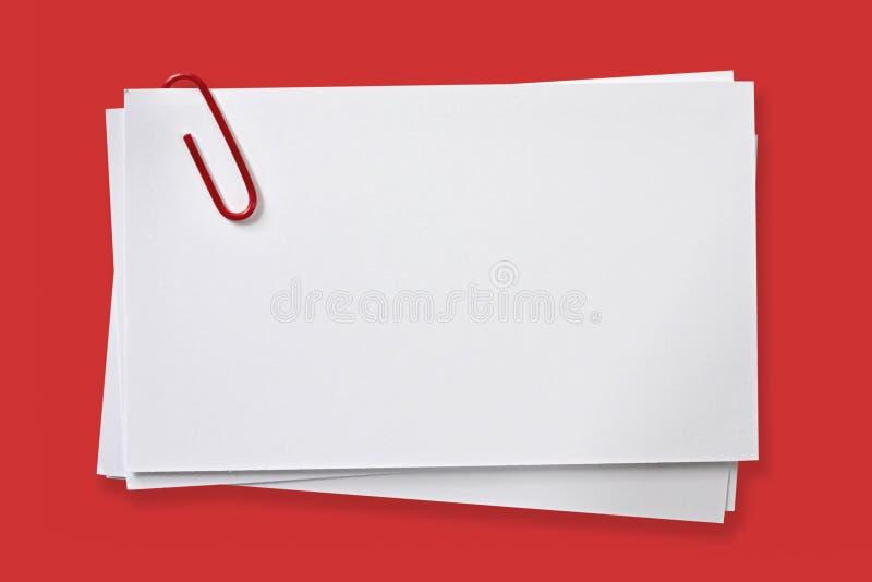 Tarjetas en blanco con el clip de papel rojo foto de archivo