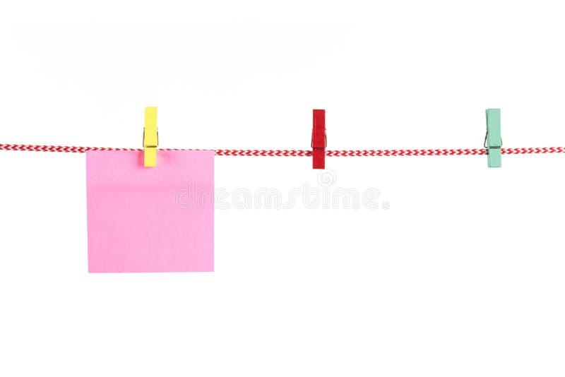 Tarjetas en blanco de papel que cuelgan en la cuerda roja aislada en el backgrou blanco imagen de archivo