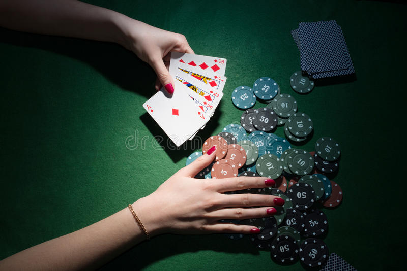Tarjetas y microprocesadores del póker a disposición en fondo verde foto de archivo