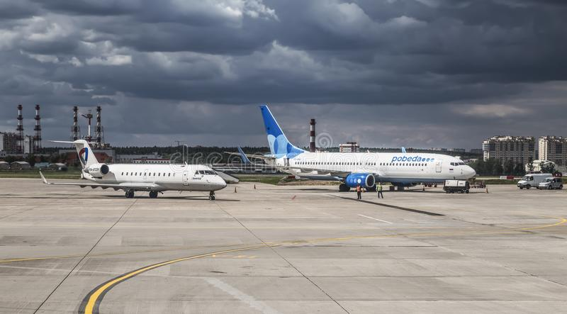 On the tarmac of the airport Vnukovo the plane of airline `Pobeda` Boeing 737-800 and the plane of airline `Severstal` Bombardier. CRJ200ER RA-67239. Moscow stock photos