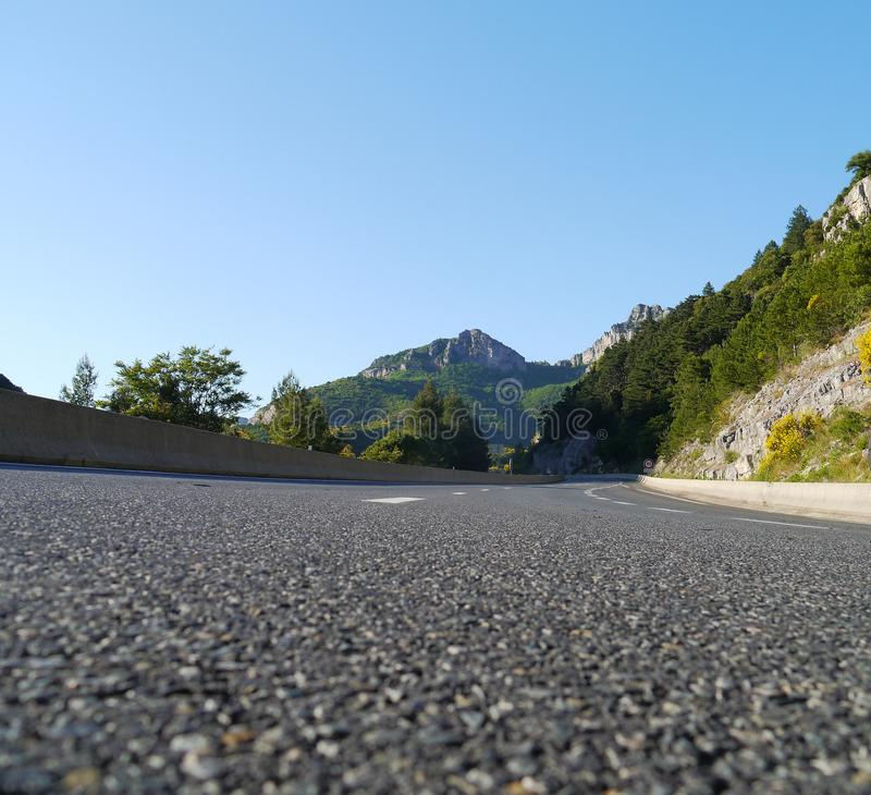 Tarmac road leading to mountians. Tarmac road leading to mountains. low level image with curving road and blue sky royalty free stock images