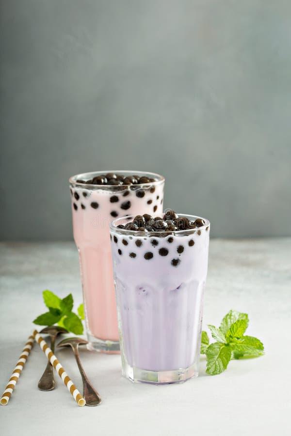 Taroen och jordgubben mjölkar bubblate i högväxta exponeringsglas fotografering för bildbyråer