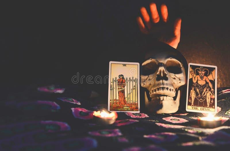Tarokkort för psykiska tarokläsningar såväl som spådom med skallestilleben och levande dödhand på mörkret arkivfoton