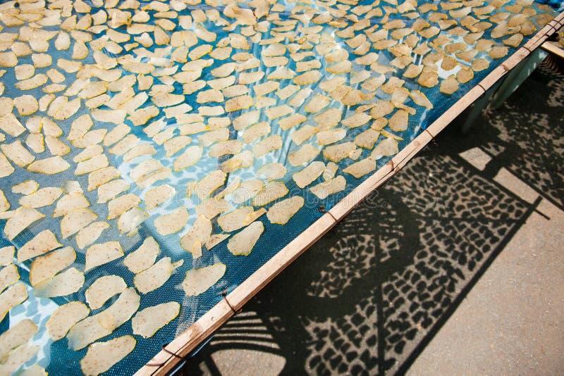 Taroplak het drogen in zonneschijn op de netto, traditionele snack van T stock fotografie