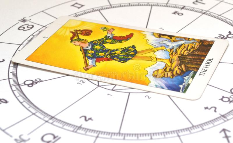 Tarot and astrology. Fool card on a astro chart. Tarot and astrology. Natal chart with the Fool Tarot card in the center.Astrology chart in the background stock photo
