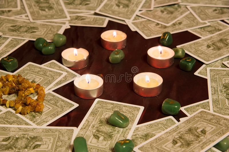 Tarot cards, burning candle and runes. Moscow, Russia - December 4, 2016: Rider-Waite tarot cards and burning candle with runes in center. Esoteric background royalty free stock photos