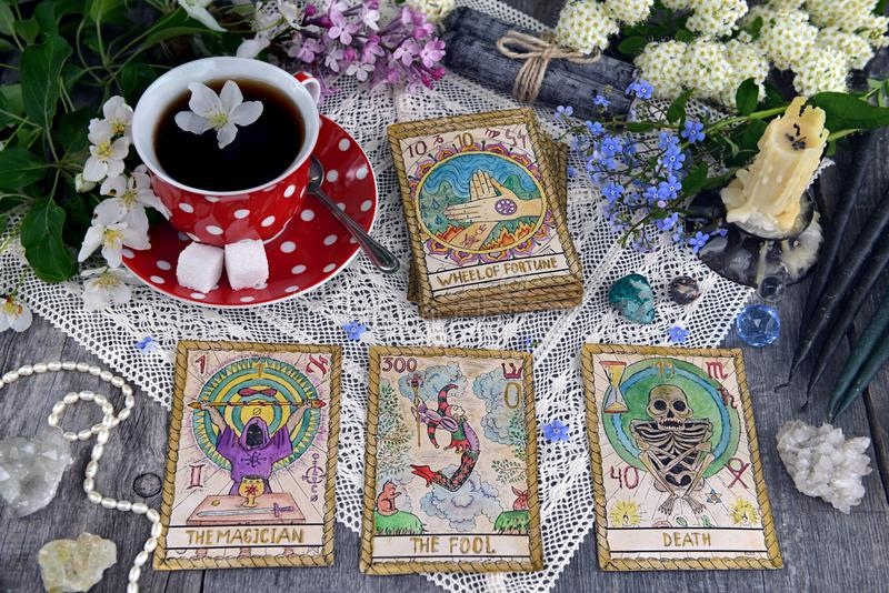 Tarot cards with cup of tea, flowers and black candles on planks royalty free stock photos