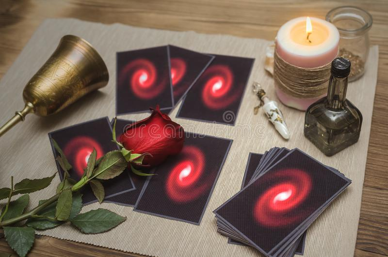 Tarot cards deck. Future reading. Fortune teller. The psychic. Tarot cards on fortune desk table, empty wine goblet and red rose flower. Future reading concept stock photography