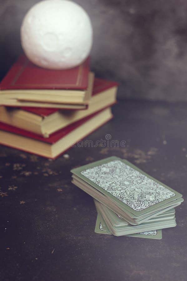 Tarot cards on fortune teller desk table. Future reading. Tarot cards on fortune teller desk table opened books moon light lamp vertical royalty free stock image