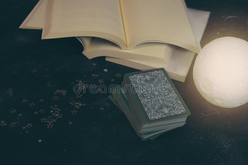 Tarot cards on fortune teller desk table. Future reading. Tarot cards on fortune teller desk table opened books moon light top view royalty free stock photography