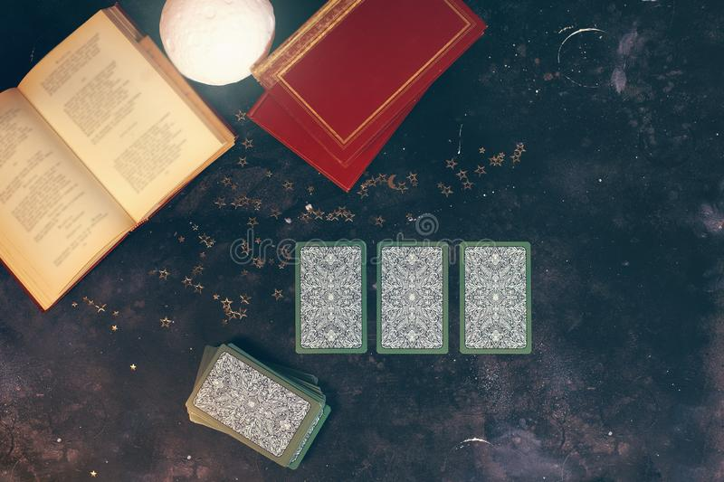Tarot cards on fortune teller desk table. Future reading. Tarot cards on fortune teller desk table opened books moon light top view stock image