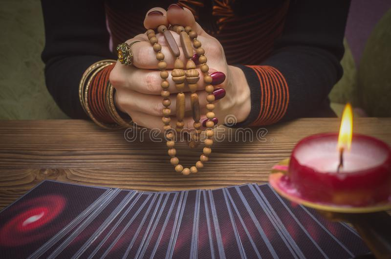 Tarot cards deck. Future reading. Fortune teller. The psychic. Tarot cards and future reading concept. Fortune teller holding in hands a rosary beads royalty free stock photos
