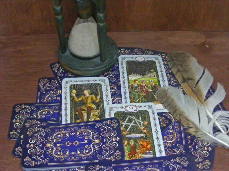 Tarot cards with owl feathers and hourglass on wooden table stock image