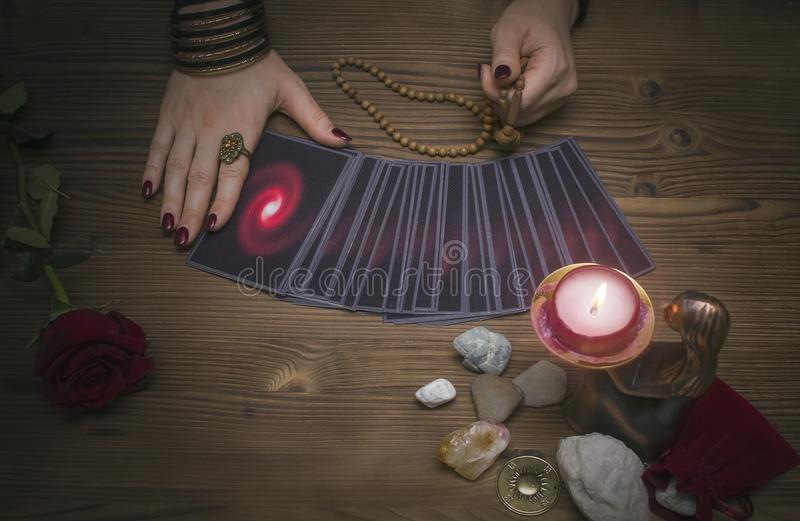 Tarot cards on the table. Fortune teller reading the future. The Psychic. Tarot cards on the table. Fortune teller reading the future and holds in hands a royalty free stock photography
