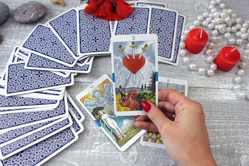 Tarot karty, świeczki i akcesoria na drewnianym stole, obraz royalty free