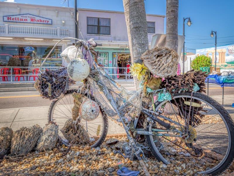 TARPON SPRINGS, FLORIDA - 30 DE JUNHO DE 2019: Arte da esponja em uma bicicleta na baixa imagem de stock