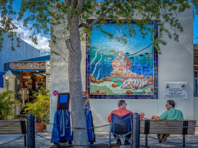 TARPON SPRINGS, FLORIDA - 30 DE JUNHO DE 2019: Os homens conversam na frente do mosaico da telha do mergulhador da esponja foto de stock