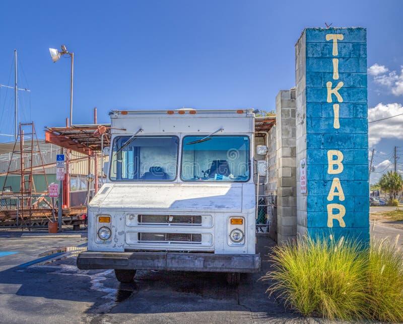 TARPON SPRINGS, FLORIDA - 30 DE JUNHO DE 2019: Sinal de Tiki Bar ao lado de um caminhão branco velho do gelado da batida acima fotografia de stock royalty free
