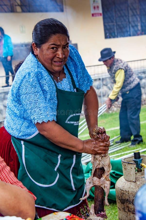 Tarqui, эквадор/4-ое октября 2015 - женщина подготавливает cuy для BBQ стоковое изображение rf