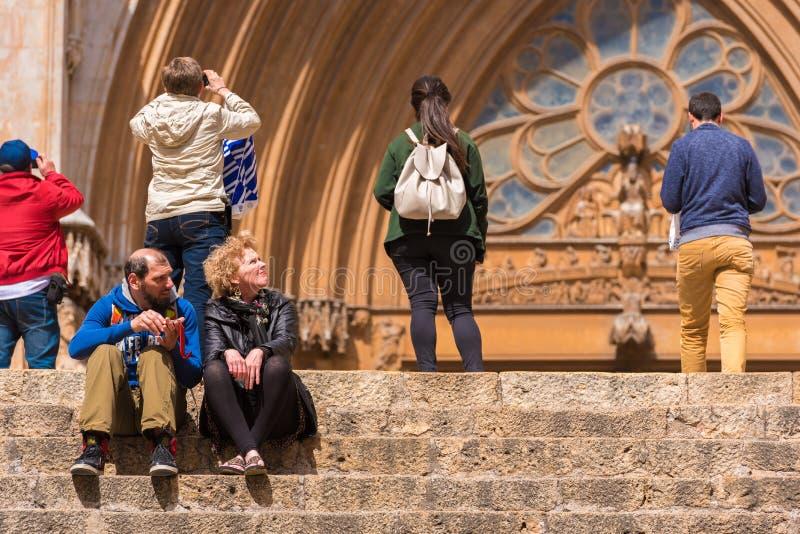 TARRAGONA, SPAGNA - 1° MAGGIO 2017: Una donna e un uomo stanno sedendo sui punti della cattedrale del cattolico della cattedrale fotografia stock libera da diritti