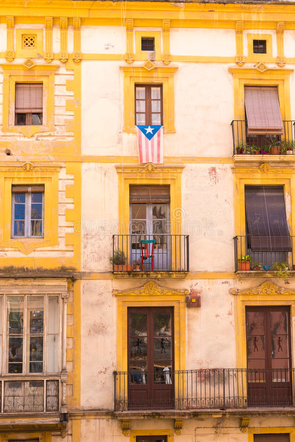 TARRAGONA, SPAIN - MAY 1, 2017: Facade of Spanish house with balconies and flowers. Close-up. Vertical. royalty free stock images