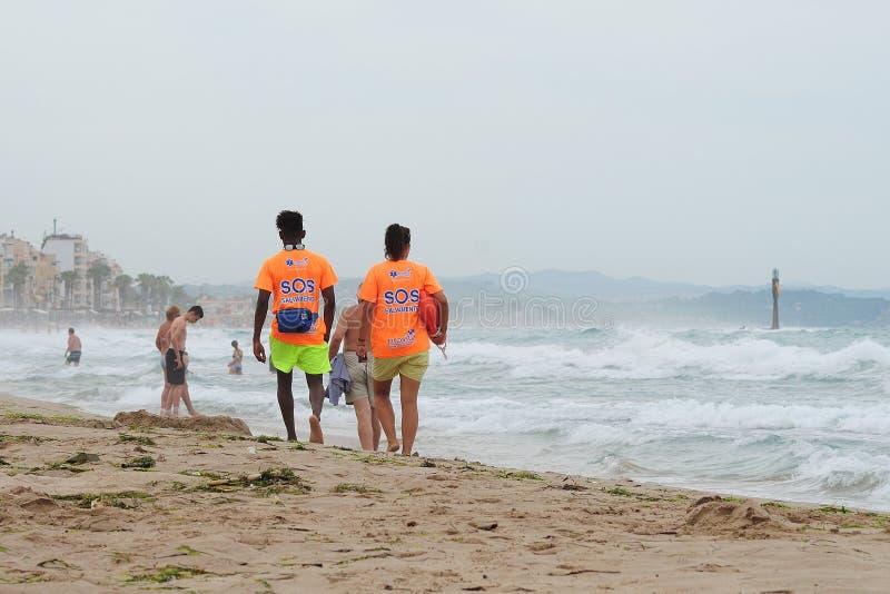 Tarragona, Spanien - 7. Juli 2017: zwei Leibwächter auf dem Strand bei schlechtem Wetter lizenzfreie stockbilder