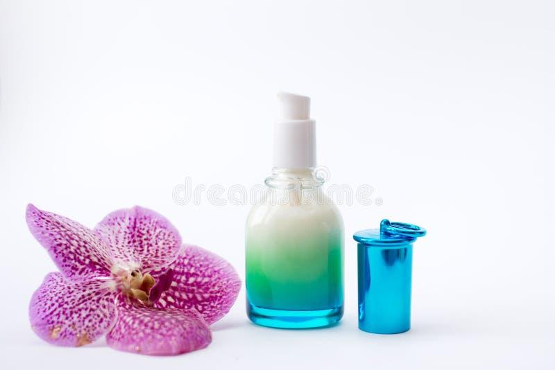 Tarro azul de la crema y de la flor en el fondo blanco, visión superior Productos cosméticos profesionales foto de archivo