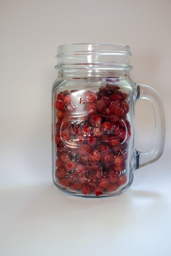 Tarro con las fresas en un fondo blanco 5 imagen de archivo