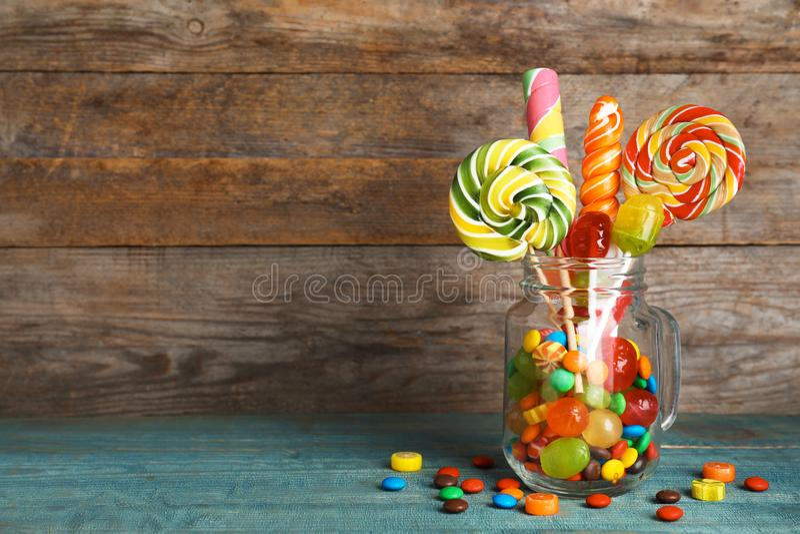 Tarro de albañil con diversos caramelos coloridos en fondo de madera imagenes de archivo