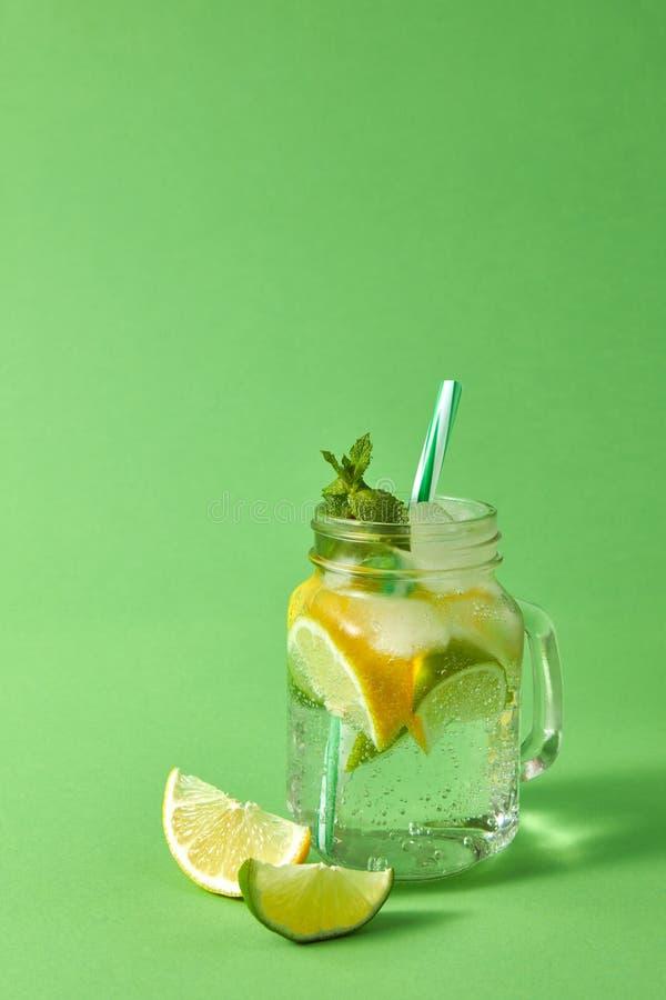 Tarro de albañil con limonada chispeante hecha en casa con hielo, rebanadas de cal y limón, hoja de la menta con la paja plástica fotografía de archivo