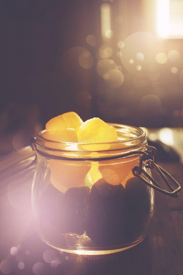 Tarro de albañil con los caramelos de la jalea en puesta del sol foto de archivo