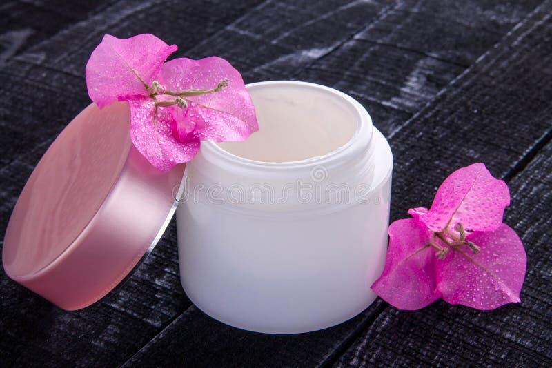Tarro de crema natural con las flores rosadas imagenes de archivo