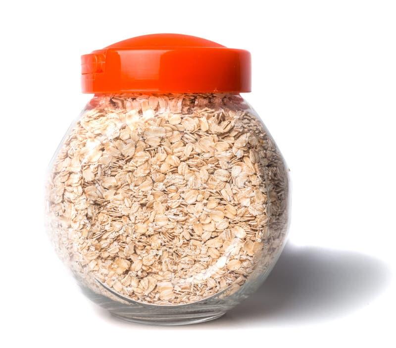Tarro de cristal abierto con la avena rodada aislada en el tarro de cristal del fondo blanco con las escamas de la harina de aven foto de archivo libre de regalías