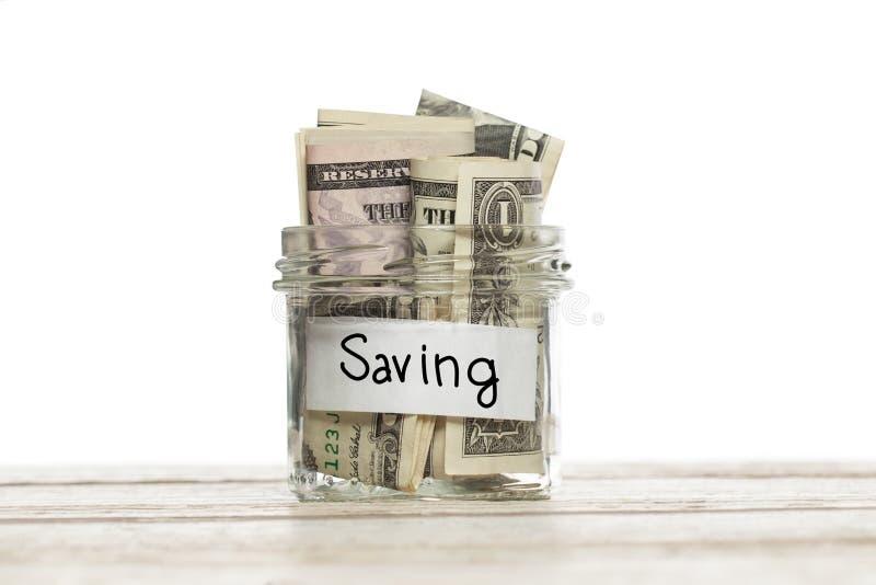 Tarro de cristal de ahorro con dólar dinero en la tabla de madera contra el fondo blanco foto de archivo libre de regalías
