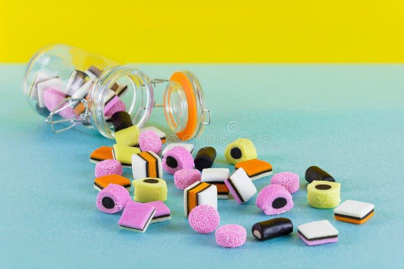 Tarro de cristal con el fondo minimalista brillante de allsorts del regaliz colorido del caramelo fotos de archivo libres de regalías