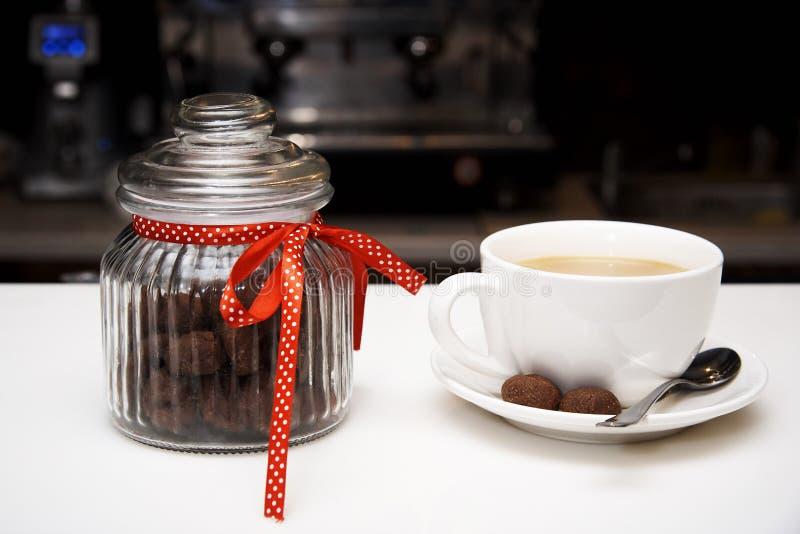 Tarro de cristal con galletas y una taza de café imagen de archivo